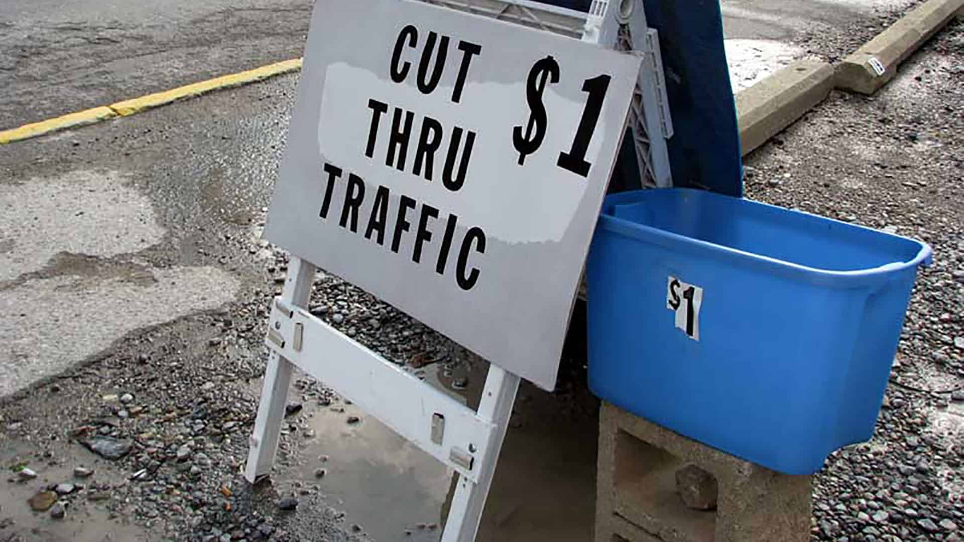 A sign reading: Cut thru traffic $1.